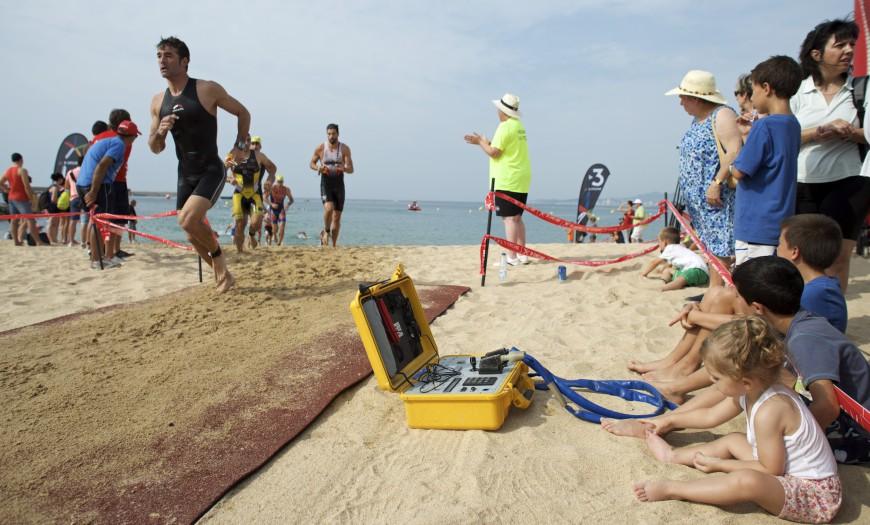 Triatletas corriendo por la playa