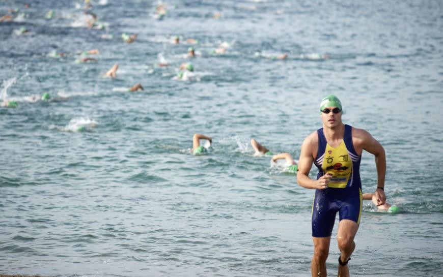 Triatletas corriendo y nadando
